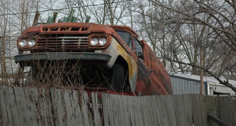Old rusted car showing over a fence