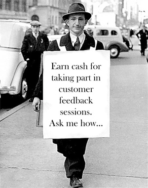 A man with a sandwich board advertising customer feedback sessions